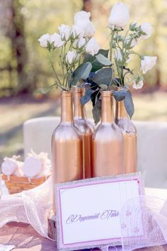Creative idea: spray painted wine bottles as vases for centerpieces, you can paint them whatever color you want to match your wedding.
