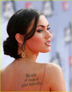 """Megan Fox has a short poem that reads """"We will all laugh at the gilded butterflies"""" on her back,"""