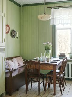 Restful green painted tongue and groove walls for this relaxed country style dining area