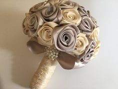 Wedding bouquet as follows:  Colors- Taupe/Cream  For- Bride/ Bridesmaid Size- Approximately 15 in diameter 12  long.  Handle-cream Handle- braided in in Ivory Organza ribbon.  Handle- Crystal pins.  Several colors to choose from.  Free color swatches available. All roses handmade by specialtouchroses from 2 1/4 satin ribbon  Priority mail for all orders.