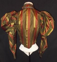 This exceptional bodice dates to the Victorian 1890's and is fashioned of a rich patterned striped French silk jacquard with massive balloon puffs atop the shoulders, fitted bottom sleeves with stiff buckram lined bottom cuffs trimmed in metallic braid and small shimmering sequins that matches the trimming of the high band collar. The collar hooks closed at a dart point, fully boned in the interior and lined in polished cotton. The only flaw is that several small sequins are absent and a…