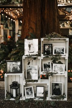 Stacked white crates filled with black and white photos of the bride and groom, eucalyptus, and lanterns for a personal decor statement that's both refined and rustic.