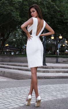 Nova, an edgy bandage bodycon dress is innocent in all white but shows a lot of strategic skin with a deep cut neckline, side boob features and straps that extend over the shoulders exposing the back.