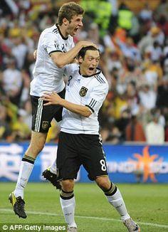 Lesson in love: Thomas Muller celebrates with Mesut Ozil...