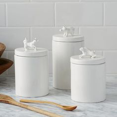 Knockoff West Elm Animal Cannisters: Glue an animal figurine to the top of a flat canister without a handle, spray paint the whole thing glossy white.