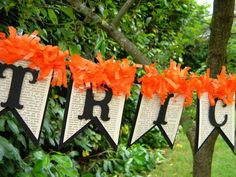 Pages of an old book, black construction paper, and orange tissue paper to make a Halloween message banner (you could do this for any holidy - just change the colors)