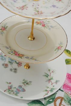 This cosmopolitan cakestand features delicate pastels on fine china made in England, Japan and America. Excellent condition.    Top Plate - New Ivory, Hoya China Corp, Japan    Middle Plate - Eggshell, Georgian, Homer Laughlin, Made in USA, M44N5    Base Plate - Wedgwood, Bone China, Made in England, Lemon Tree