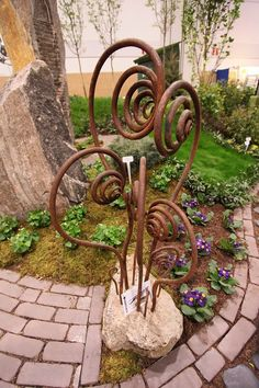 Metal landscape and garden decor creates a lovely counterpoint to the lush delicacy of plants and flowers.