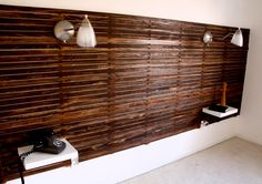 Slatted headboard with sconces and built in side shelves.