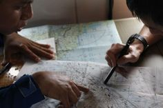 A Japan Coast Guard member studies a map with a Malaysian Maritime Enforcement Agency pilot (L) in JCG's Gulfstream V Jet aircraft customized for search and rescue operations as they search for the missing Malaysia Airlines MH370 plane over the waters of the South China Sea March 15, 2014. REUTERS/Edgar Su