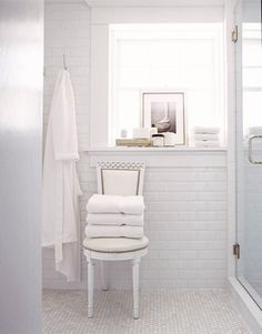 In the master bath, a Swedish-style chair covered in white vinyl substitutes for a towel bar. Walls are tiled from floor to ceiling in beveled-edge subway tile.   - HouseBeautiful.com