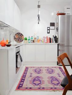 12 Kitchens & Dining Rooms Made Cozy With Kilims: PLAZA Interior featured the home of Hanna Wessman, host of Extreme Home Makeover, who added a feminine kilim to her kitchen. The rose-toned hue plays nicely with the Danish modern wood dining chairs.