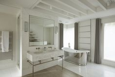 The master bathroom in this London home has a neutral palette, freestanding tub and ladder-style towel bar.