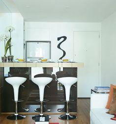 A solução para o pouco espaço, neste apartamento de 50 m², foi criar uma cozinha integrada. A pia ganhou lugar atrás do balcão revestido de vidro espelhado. Prateleiras e armários foram feitos ao lado do nicho da geladeira.