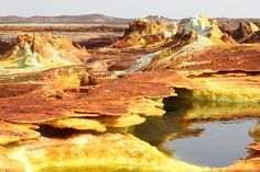 The Danakil depression in the Afar region, Ethiopia (at ~120 m below sea level), manifests itself by an incredible variety of colorful springs and fumaroles in an alian landscape of salt, sulphur and other mineral deposits.