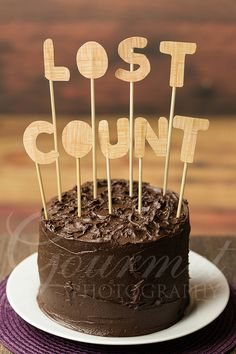 "Chocolate birthday cake with ""Lost Count"" Hand drawn and cut ""Lost Count"" (of the years) message on top of a handmade chocolate birthday cake ageing, birthday, cake, celebration, chocolate, count, dessert, lettering, food, frosted, frosting, hand cut, iced, icing, letterform, letters, lost, lost count, message, sweet, text, treat, typography, wooden, word, writing"