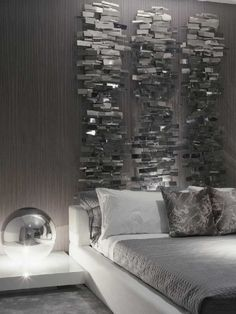 A contemporary wall sculpture above the bed draws the eye upward creating the illusion of higher ceilings.