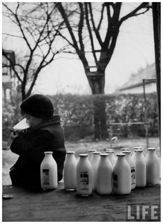 Small boy helping himself to milk, as other bottles delivered to family on every other day basis is waiting to be taken inside 1953 GordonParks