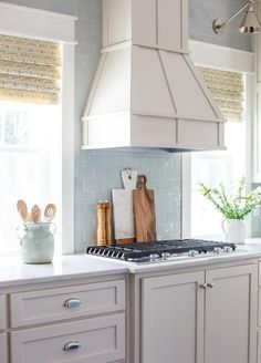 An ivory kitchen hood stands over a blue glass tile backsplash and an integrated gas cooktop flanked by windows lit by Boston Functional Library Wall Lights.