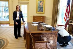 President Barack Obama examines the Resolute Desk on March 3, 2009, while visiting with Caroline Kennedy Schlossberg in the Oval Office. In a famous photograph, her brother John F. Kennedy Jr., peeked through the FDR panel, while his father President Kennedy worked.
