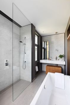 The adjoining master bathroom is connected by mirrored pocket door with bronze trim at the frame. The graphic space features a Kaldewei tub, Domus tiles, and Dornbracht faucets and fixtures. Large Tile Bathroom, Bathroom Renos, Bathroom Renovations, Bathroom Ideas, Concrete Bathroom, Bathroom Faucets, Modern Contemporary Bathrooms, Home Modern, Modern Bathroom