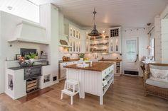 Tyylipuhdasta maalaisromantiikkaa! Isolla saarekkeella ja puuhellalla varustettu keittiö on ihanan kodikas.