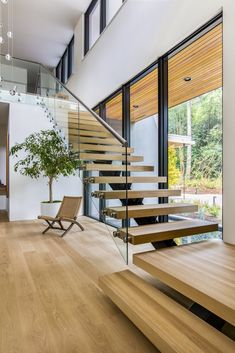Staircase, Wood Tread, and Glass Railing Set on top of a forested ridge separating downtown Portland and the suburban sprawl of Beaverton, OR, Wildwood by Giulietti / Schouten AIA Architects is a rural retreat and primary residence hidden within the metro area of the Pacific Northwest. The floating staircase features glass guardrails and white oak treads to match the hardwood floors.