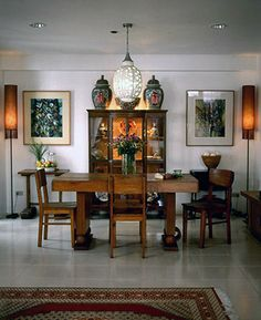 A narra dining set from the 1950%u2019s is the central focus of the dining area. Surrounding it is a china cabinet with a collection of red and white jars and plates. Setting a formal balance to the space are jars on top of the cabinet, lamps with shawl lampshades, and abstract paintings.�