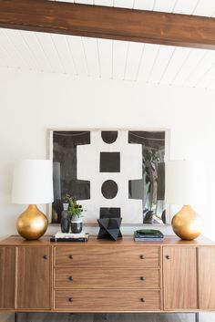 Mid Century Home With Modern Artwork And Natural Wood Cabinet