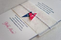 Nautical wedding invitation with red and navy flags wrapped in twine.