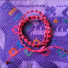 """Hot Pink """"Xubal Handmade Bracelet from Guatemala"""" In Hot Pink with black beads, 26"""" around, 100% Poly Waxed Thread, Metal Beads, Handmade by skilled artisans in Guatemala, mix & match! For sale as individuals or with Ketzali """"Tzuel Textile Pouch""""- $32., with Makeup bag- $42, with Makeup bag, Pouch, and 1 Bracelet- $58, with 2 Bracelets- $72. Ketzali Jewelry Bracelets"""