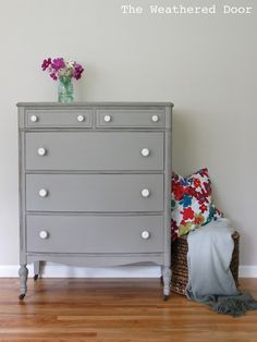 A distressed elephant grey dresser with white knobs