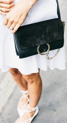 Jacey Duprie is wearing a white mosaic Tibi dress with a black suede Chloe Small Faye clutch side bag