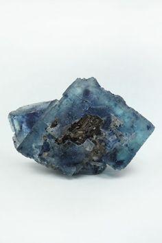 Specimenul de Fluorina prezinta un cristal crescut peste o cristalizare de Pirotina cu un frumos luciu metalic, cristalizare hexagonala sub forma de lamele suprapuse. Muchiile intacte ale cristalelor de Fluorina sunt drepte si ascutite, o frumoasa culoare de albastru deschis accentuata in interior de fantomele mov. Specimenul prezinta doua cristalizari de Siderit, una dintre ele formand o mica floare cu cristale romboedrice, cu fețe curbate. Decorative Bowls, Amethyst, Texture, Crystals, Abstract, Crafts, Surface Finish, Summary, Manualidades