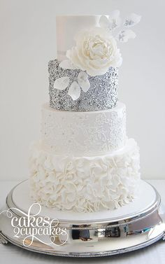 Silver and white wedding cake with flower accent & Sequin Wedding Cakes with metallic gold and silver accents via The Magazine White Wedding Cakes, Cool Wedding Cakes, Beautiful Wedding Cakes, Gorgeous Cakes, Wedding Cake Designs, Bling Wedding Cakes, Fondant Wedding Cakes, Wedding Cake White, Textured Wedding Cakes