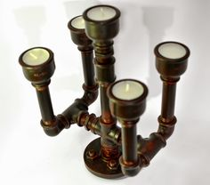 Industrial style metal candlestick. It is made of metal pipe fittings, distressed using coloring processes. For 5 candles