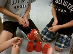 Great team work idea. The strings are tied to a rubber band. Can they work together to pick up the cups and build a pyramid out of them only by holding their own string?