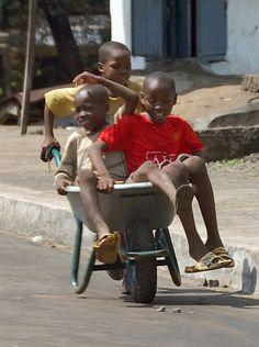 Boys playing in a wheelbarrow, Monrovia, Liberia
