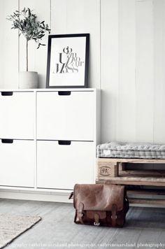 biała wisząca szafka na buty,siedzisko z drewnianej palety,pikowane poduszki w paski,białe panele na ścianie,szara podłoga z desek w przedpokoju w stylu skandynawskim - Lovingit.pl