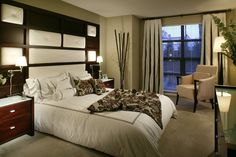 Romantic master bedroom with an upholstered headboard, modern bedside tables and a dark brown painted accent wall. #painting #headboards