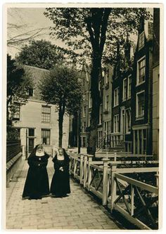 1935 - 1940. Two nuns walking at the east-side of the Begijnhof. Founded during the Middle Ages, The Begijnhof is one of the oldest inner courtyards of Amsterdam. It lies within the Singel — the innermost canal of Amsterdam's circular canal system. It is unclear when exactly The Begijnhof was founded. In 1346, the beguines still lived in a house. A courtyard was only first mentioned in 1389. Photo De Bijenkorf. #amsterdam#1940 #begijnhof