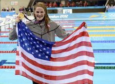Missy Franklin, 17, holds up an American flag after winning the gold medal in the women's 100-meter backstroke Monday.