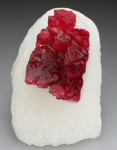 Spinel crystal on snow white marble.  But it looks like cherry ice on snow!  Tasty on a very hot day...like today.  http://crystalclassics.co.uk/hall-of-fame/detail.php?id=3068