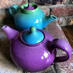 Colorful teapots! Both made from white earthenware clay and hand thrown and built. They have been spray glazed in purple and sky blue with a hint of yellow to create the green around the top of each.
