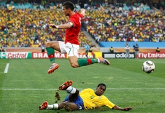 Cristiano Ronaldo evades a tackle by Brazil's Juan - World Cup 2010 Group G, Moses Mabhida stadium, Durban June 25, 2010. (REUTERS/Yves Herman)
