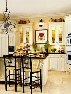 One of many kitchen ideas-I like the contrast of the black chairs w/white cabinets and soft yellow walls