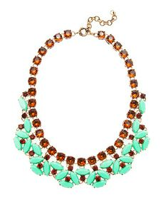 make a necklace with eyes coming off (imagine the blue bits are the upper and lower lids, and the orange gems within them are the pupils) easy now