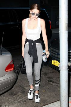 Laid back:The 21-year-old budding model donned a pair of washed out grey leggings, a simple white tank top and a black sweater which she effortlessly tied around her waist