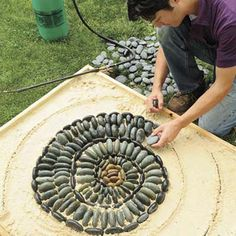 """Three ways to make a pebble mosaic. One is to work in small molds, build a mold, pour a cement mix into the bottom and arrange your pebbles on top. A second is the """"upside-down"""" method, one builds a mold and pours a layer of sand into it, then arrange your stones in the sand and fill the top with cement. When dry remove  mold and brush away sand. Third way, have everything prepared and by your side, and then pour small areas of cement , onto the prepared subsurface and push stones into…"""