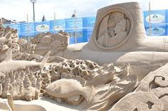 Sand sculpture: Man in submarine watching sea life from a porthole ... fish, coral,  #sand  #art